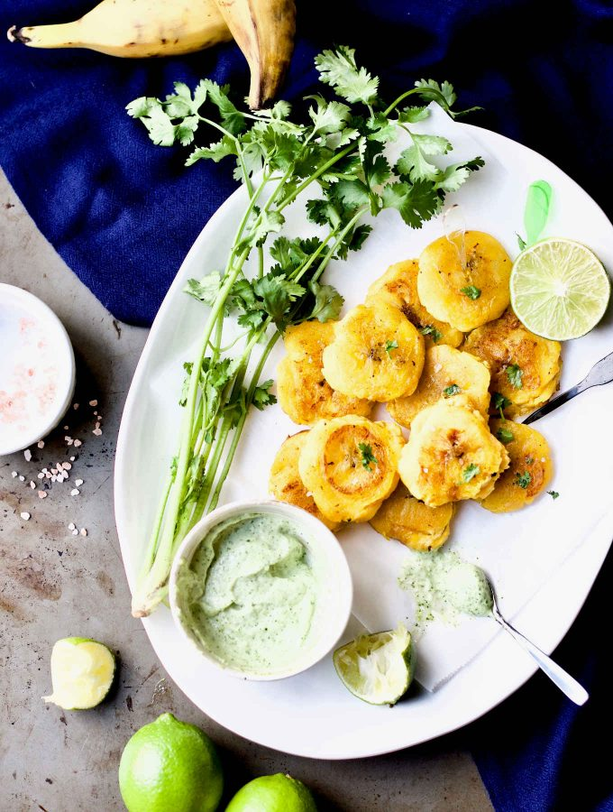 """Overhead shot of the tostones/patacones (twice-fried green plantains) paired with garlic cilantro mayonnaise (salsa de ajo), from the """"Latin American Paleo Cooking"""" cookbook."""