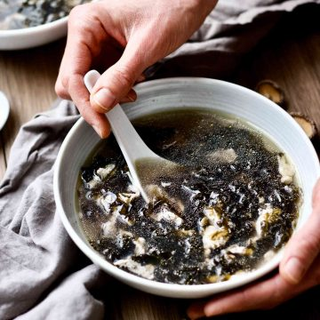 a bowl of chicken broth seaweed egg drop soup.