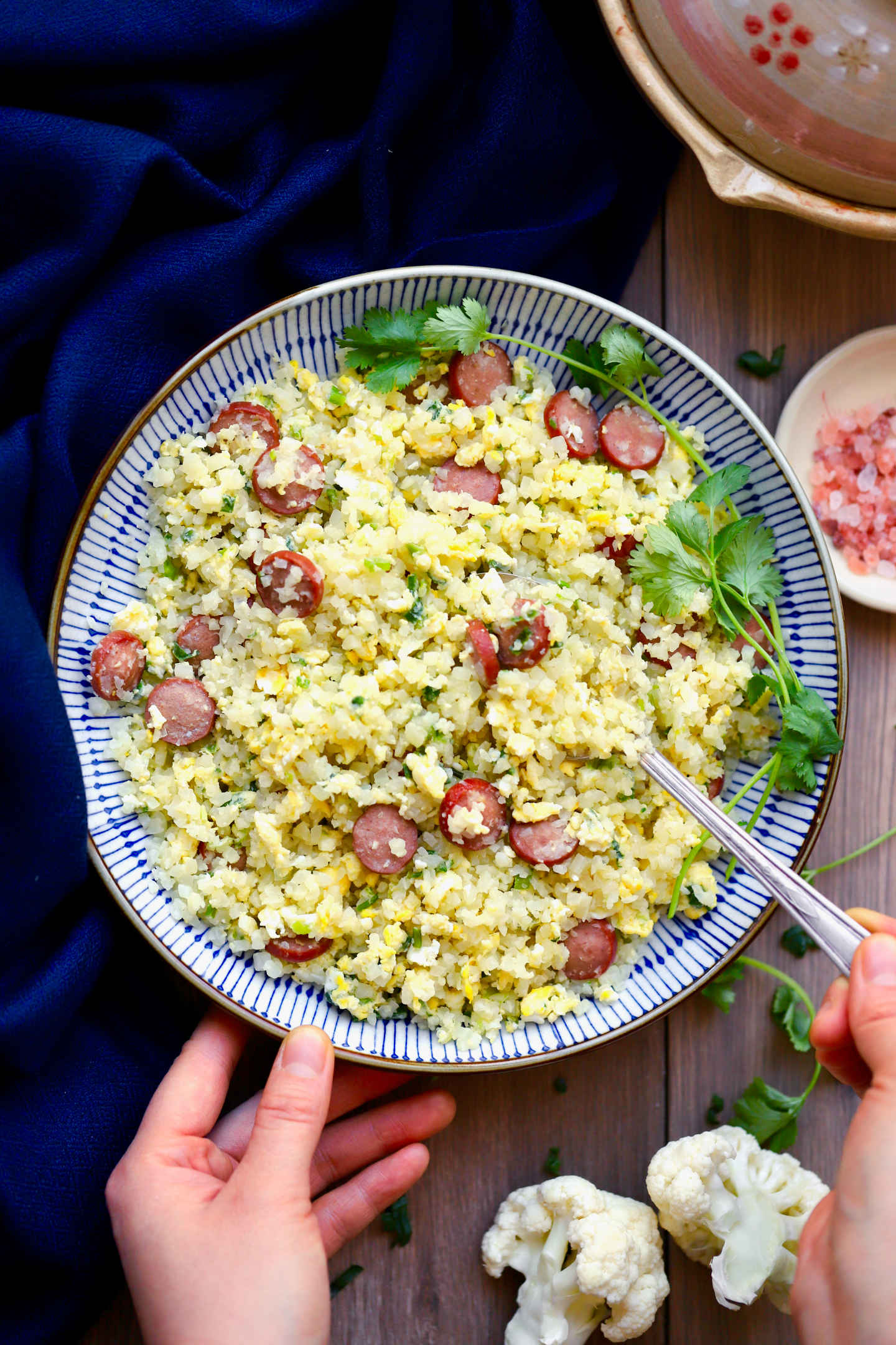 a plateful of egg and hot dog fried rice, served with a spoon