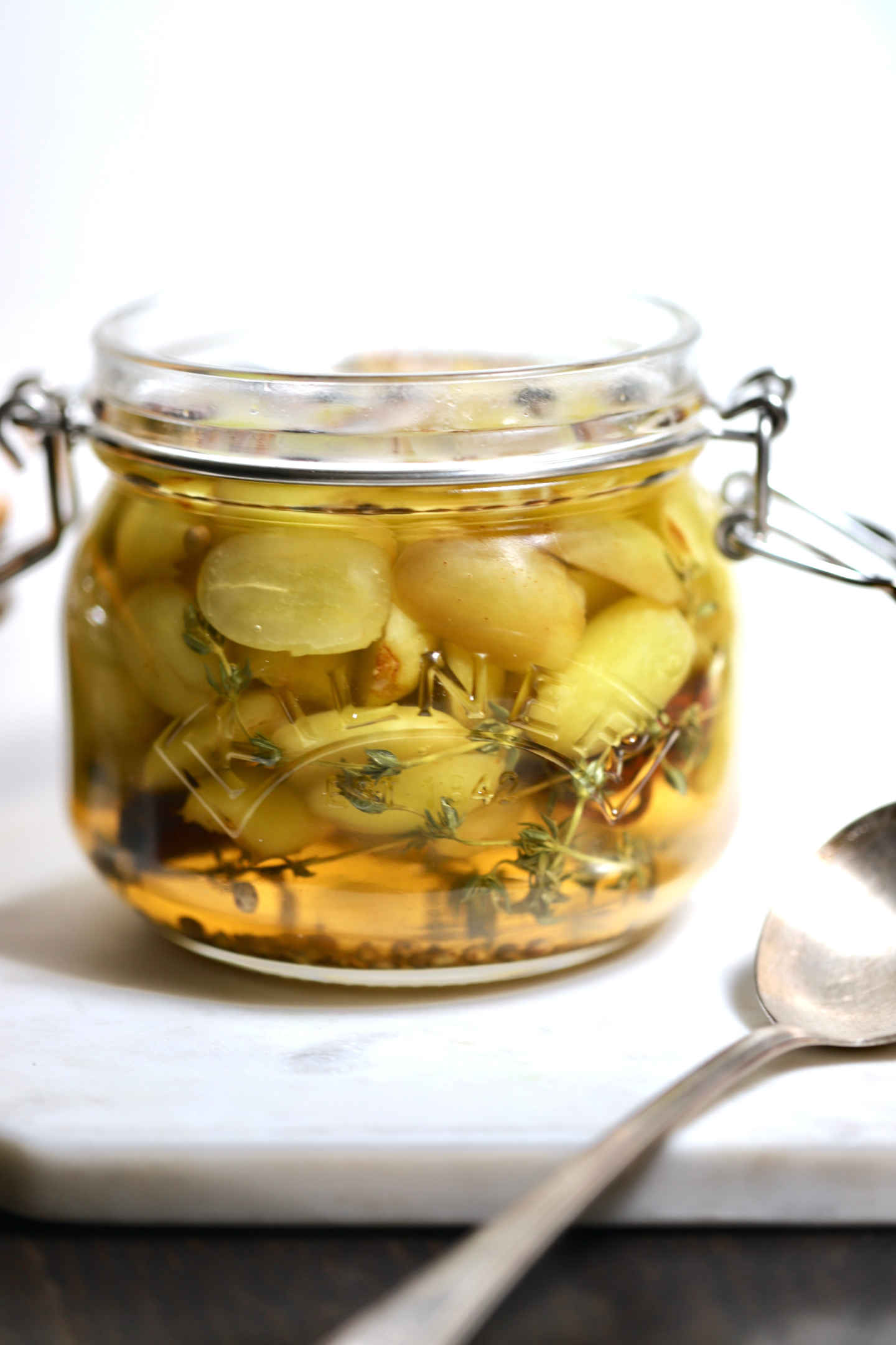 green grapes pickling in a jar with spices and white wine vinegar