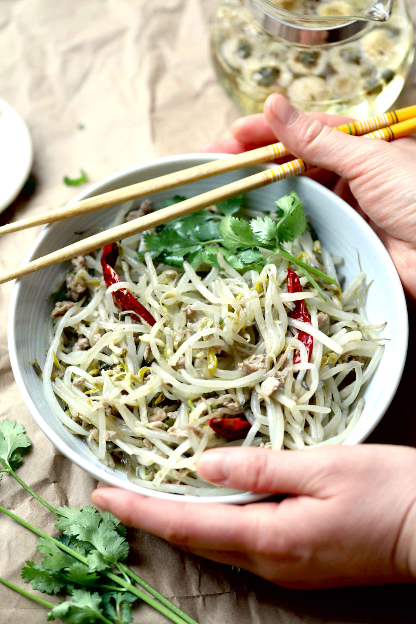 hands holding a dish of bean sprouts and a pair of chopsticks