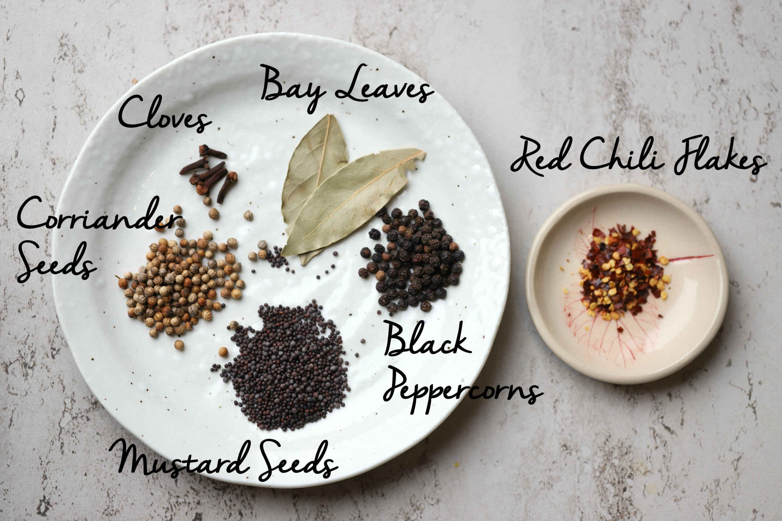 spices for the pickling brine: cloves, bay leaves, black peppercorn, mustard seeds, coriander seeds, chili flakes