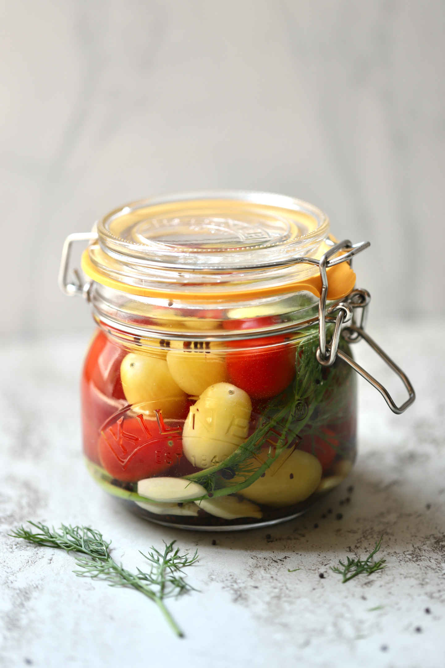 red and yellow cherry tomatoes fermenting in a jar
